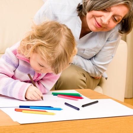 Grandmother and little girl drawing together with pencils at home Stock Photo - 12079934