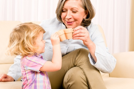 Grandmother with little girl drink tiny cups toasting happy home Stock Photo - 12079940