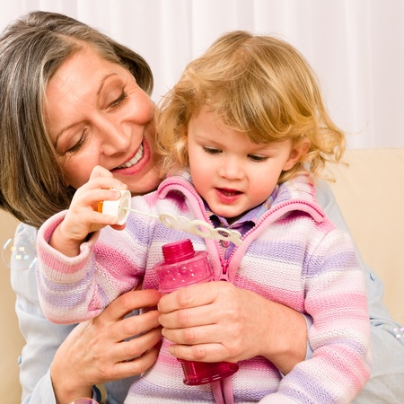 Little granddaughter with grandmother make bubble blower play happy together Stock Photo - 12079938