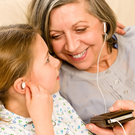 Granddaughter and grandmother listen to MP3 music headphones together smiling photo