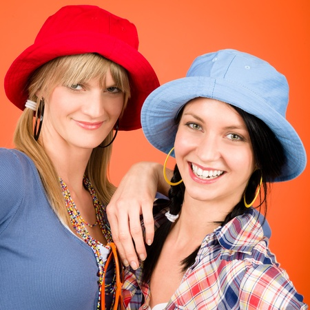 two women hugging: Two woman friends young wear funny hats smiling crazy outfit