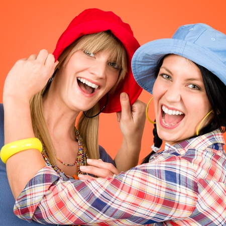 Two woman friends young wear funny hats smiling crazy outfit Stock Photo - 12343429