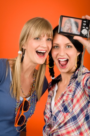party outfit: Two young woman friends taking picture with camera orange background