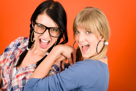 two women hugging: Two woman friends young have fun crazy smiling orange background