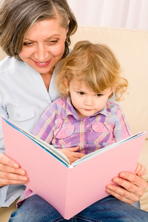 Grandmother and little girl reading book happy together at home Stock Photo - 12343476