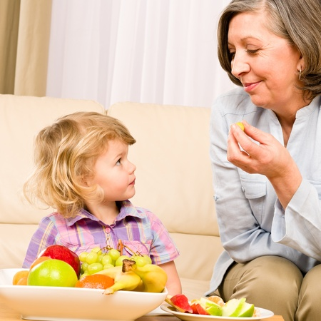 Little girl watch grandmother eat fruit relaxing on sofa Stock Photo - 12343468