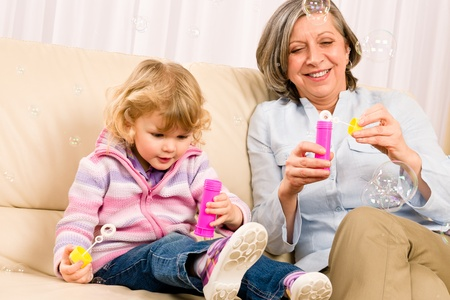 Little granddaughter with grandmother make bubble blower play happy together Stock Photo - 12343474