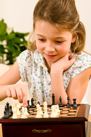 Young girl play chess cute smile alone at home photo