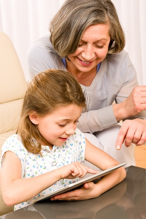grandmother and children: Grandmother with young girl use touch screen tablet computer smiling Stock Photo