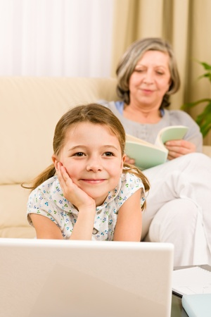 Young girl using computer laptop while grandmother read book at home photo