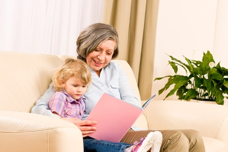 Grandmother and little girl reading book happy together at home photo