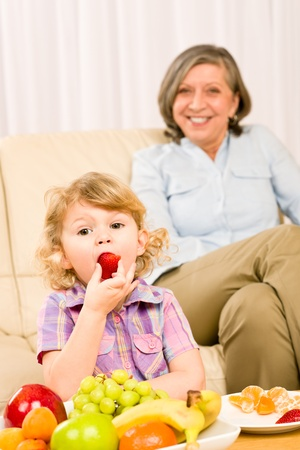 Little girl eat strawberry fruit with grandmother relaxing on sofa Stock Photo - 12343480