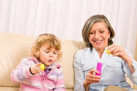 Little granddaughter with grandmother make bubble blower play happy together Stock Photo - 12343481