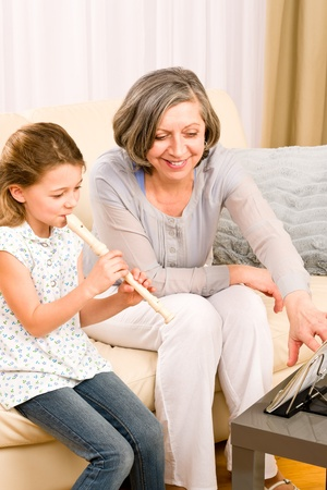 Grandmother teach young girl to play flute happy sitting on sofa photo