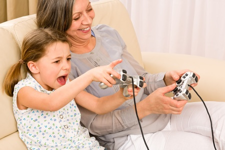 Grandmother play computer game with enthusiastic young girl have fun smiling photo