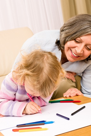 Grandmother and little girl drawing together with pencils at home photo