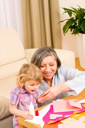 Grandmother with granddaughter playing together glue hearts on paper photo