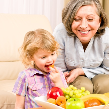 Little girl eat apricot fruit with grandmother relaxing on sofa Stock Photo - 12343452