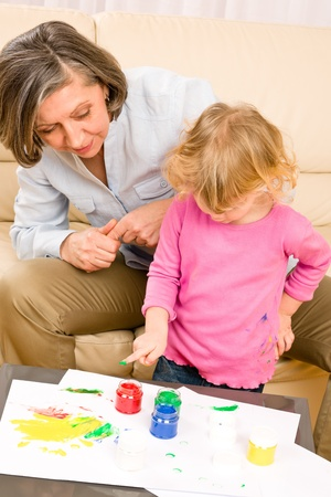 Grandmother with granddaughter playing together paint handprints on paper Stock Photo - 12343461