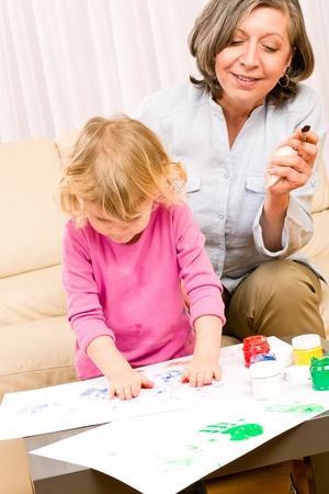 Grandmother with granddaughter playing together paint handprints on paper Stock Photo - 12343458