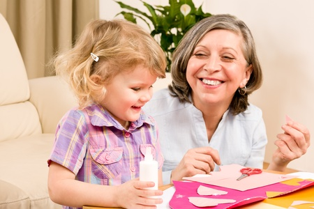 Grandmother with granddaughter playing together glue hearts on paper Stock Photo - 12343554