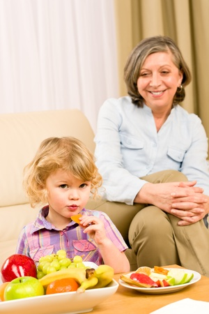 Little girl eat apricot fruit with grandmother relaxing on sofa Stock Photo - 12343549