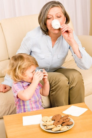 Little granddaughter with grandmother eat cookies drink tea cup together Stock Photo - 12343553