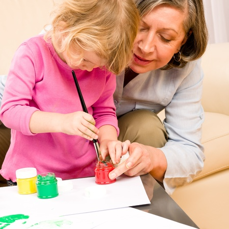 Grandmother with granddaughter playing together paint handprints on paper Stock Photo - 12343548