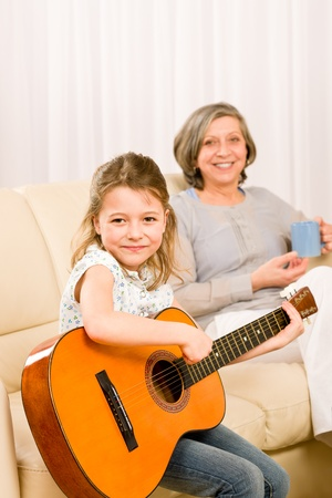 Young girl granddaughter sing play guitar to grandmother smile photo