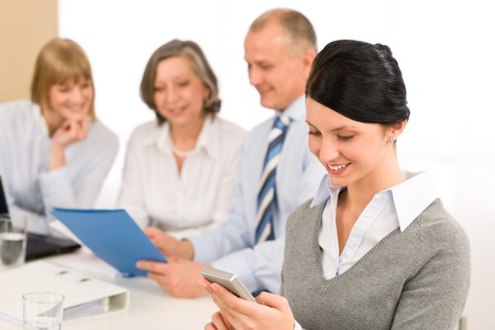 office use: Young executive woman use phone during meeting with team colleagues Stock Photo