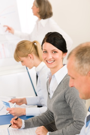 flipchart: Giving presentation young executive during meeting woman pointing at flip-chart