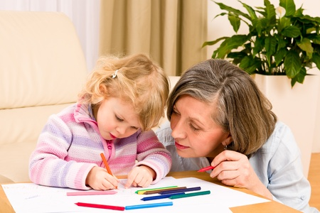 Grandmother and granddaughter drawing together with pencils at home Stock Photo - 12343540