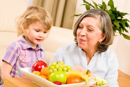 Grandmother with little granddaughter eating fruit happy together at home