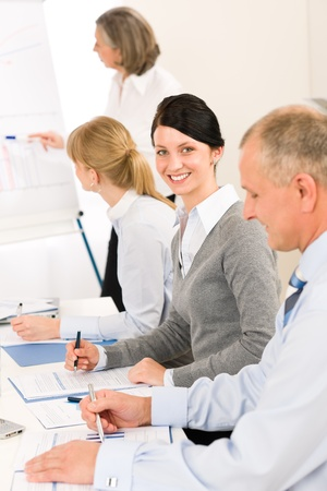 Giving presentation young executive during meeting woman pointing flip chart Stock Photo - 12343600