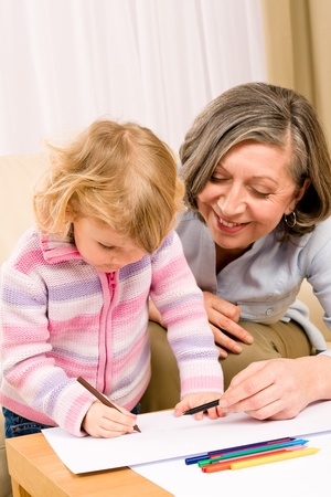 Grandmother and little girl drawing together with pencils at home Stock Photo - 12343569