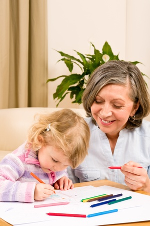 Grandmother and granddaughter drawing together with pencils at home photo