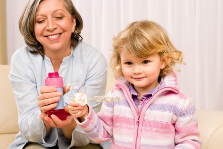 Little granddaughter with grandmother make bubble blower play happy together Stock Photo - 12343607