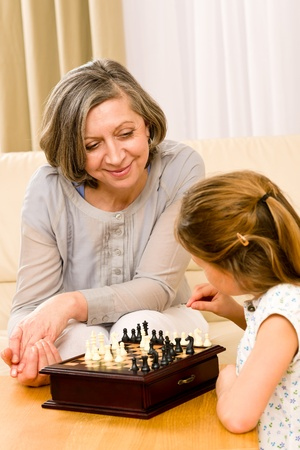 Young girl playing chess with grandmother together at home photo