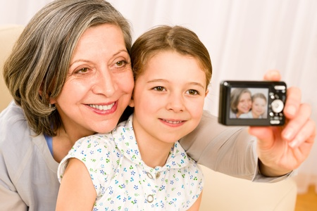 Grandmother and granddaughter take picture themselves smiling close-up portrait photo