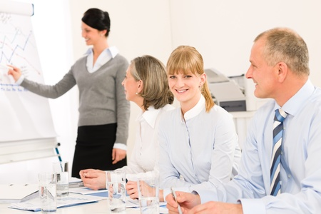 Giving presentation young executive during meeting woman pointing flip chart Stock Photo - 12343577