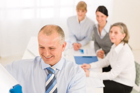 Giving presentation executive businessman pointing at flip chart team looking Stock Photo - 12343642
