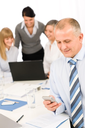 office use: Confident businessman use phone during meeting with team colleagues