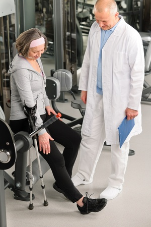 Senior woman with crutches getting help of physiotherapist at gym Stock Photo - 12343682