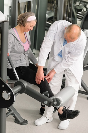 Physical therapist male assist active senior woman exercise at gym photo