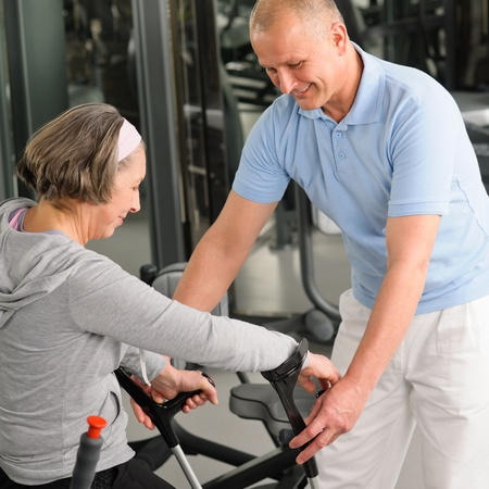 therapist: Senior woman with crutches getting help of physiotherapist at gym
