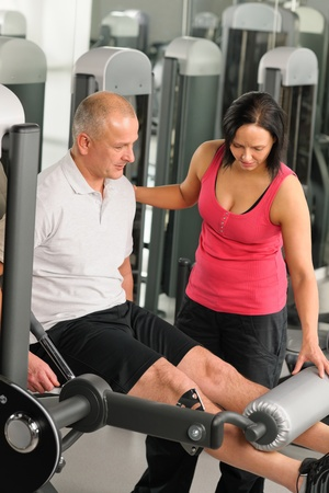 Fitness center active man exercising legs with personal trainer Stock Photo - 12343680