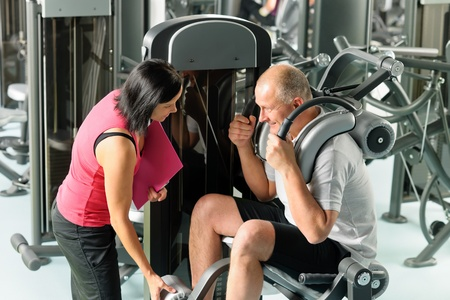 Mature man exercising at gym under supervision of personal trainer Stock Photo - 12343684