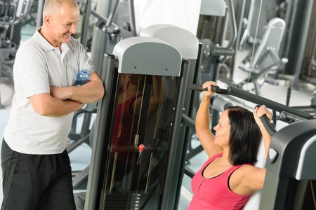 Personal trainer at fitness center showing exercise to active man Stock Photo - 12343679