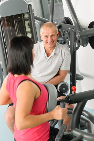 Active man watch personal trainer show exercise on gym machine Stock Photo - 12343678