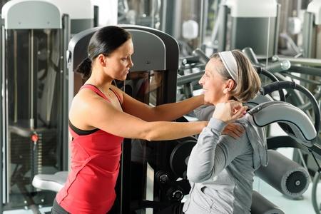 aide � la personne: Centre de fitness exercice femme �g�e avec un entra�neur personnel sur la machine